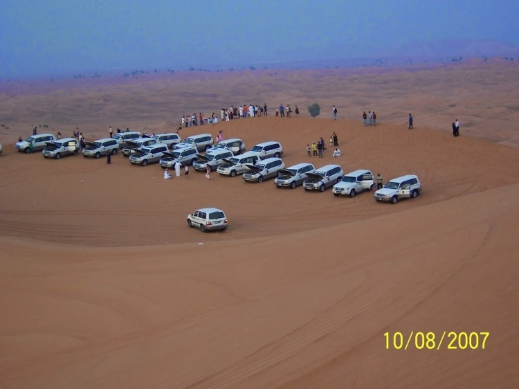View of vehicles at the middle of the safari for tourists to enjoy the desert and take photographs