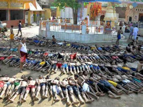 Tribal farmers lie with sticks outside Shiva temple as they wait for blessings from the main priest of the temple