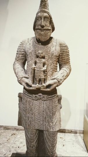 A limestone statue representing one of the leaders in the army of Hatra, wearing his Military uniform and holding a baby, found in the fourth temple in Hatra (312-139 BCE).