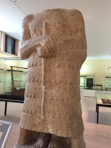 A white limestone headless statue (it lost the head) on its base with cuneiform writing mentioning the King (E-kizal-ki) and the name of the presenter (Il-La), who presented this statue to the God (Nin-kish-zida) dated to early Dynastic period (2600-2370 BCE), National Museum of Iraq, Baghdad.