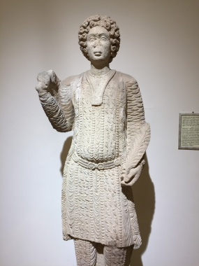 Alabaster statue of a young prince dressed in Parthian style with loose trousers, long belted tunic, and carrying acunthus leaves in his left hand and the right hand raised for greeting found in the city of Hatra (312-139 BCE), National Museum of Iraq, Baghdad.