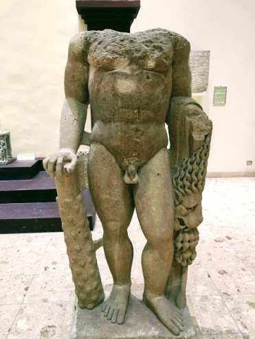 A statue of Alabaster without head of Hercules in his naked body holding a mace in his right hand and lion skin hanging from his left hand. Hercules was a god of physical strength and victory. He was the idol of soldiers. This statue was found in the ninth temple in the city of Hatra (312-139 BCE), National Museum of Iraq, Baghdad.
